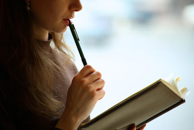 ペンを口に当てる女性