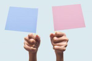 青い紙と赤い紙を持つ手